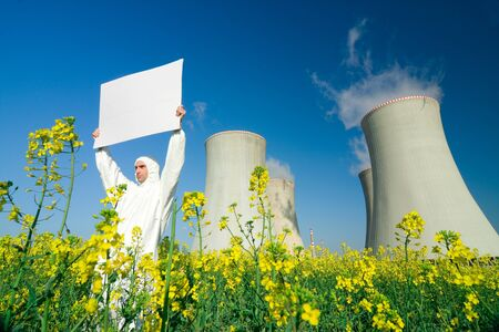 upraised: A view of a man in a protective suit, holding a blank sign in front of a nuclear power plant. Stock Photo