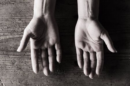 palm lined: Pair of lined senior persons hands with grainy wood background, black and white image.