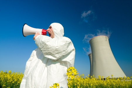 Man wearing a white jumpsuit yells into a megaphone in front of a power plant. photo