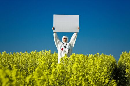 upraised: A view of a man standing in a field of yellow flowers, holding a large blank sign while wearing a white jumpsuit and carrying a large bullhorn.