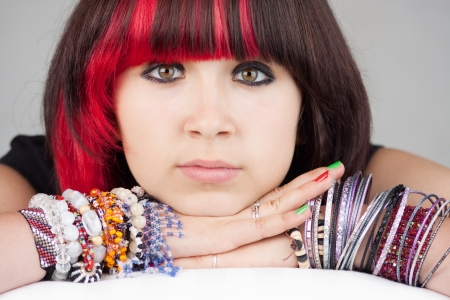 Closeup of a serious teenage girl leaning on her arms, wearing multiple colorful bracelets and pink/red highlights in her hair