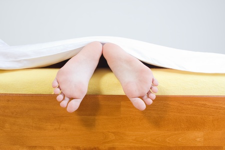 A closeup view of two bare feet sticking out from under a blanket at the end of a bed.