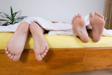 Two pairs of feet under sheets hanging over the edge of a bed. photo