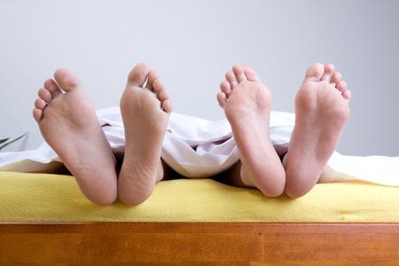 Zwei Paare von Füße unter Blätter hängen über den Rand des Bettes. Standard-Bild
