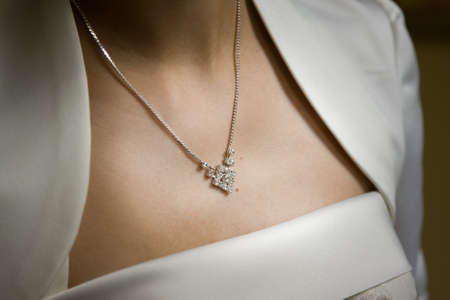 Woman in white dress wearing diamond necklace. photo