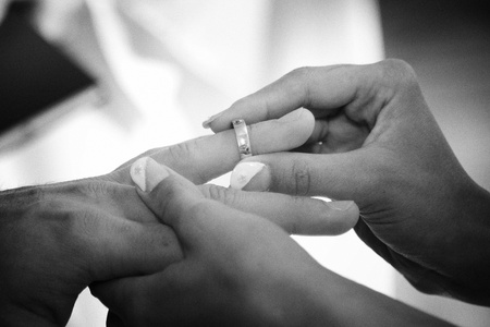 Closeup of bride placing wedding ring on finger of groom. photo