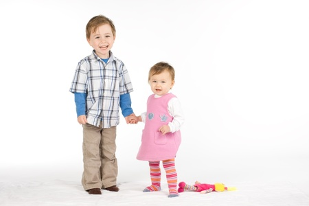 jovial: Cute siblings in a jovial mood, on a white studio background. Stock Photo
