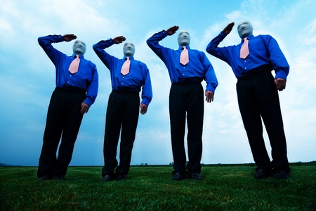 Group of four male figures stand tall against blue sky background. Men have stocking covering over faces to obscure identity.