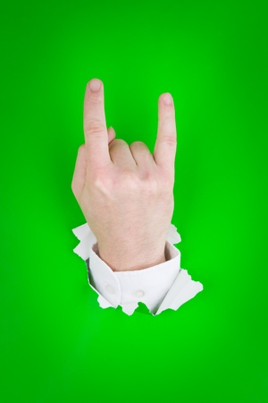 Hand sign of the horns coming through torn green paper. photo