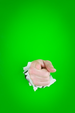 Close up of pointing finger on human hand protruding through torn green background. photo