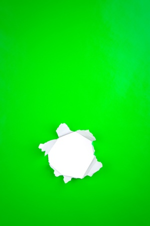 Bright green paper background with white torn hole. photo