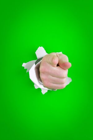 protruding: Close up of pointing finger on human hand protruding through torn green background. Stock Photo