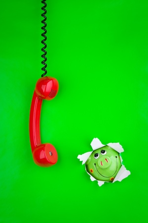 Red phone handset with black cord and a piggy bank in a torn hole through green paper background. photo