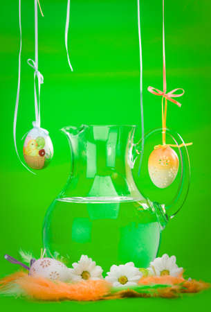 glass flagon filled with water and decorated eggs, colored feathers and daisy photo