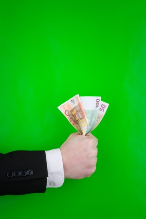 installment: A hand of an executive holding Euro notes, on a green background.