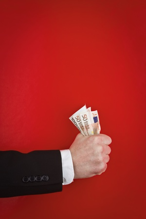 A closeup view of the forearm and hand of a man in a business suit, holding a fist full of paper money against a red background. photo