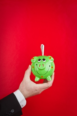 metaphorical: An executives hand holding a green piggy bank stuffed with money, on a red background.