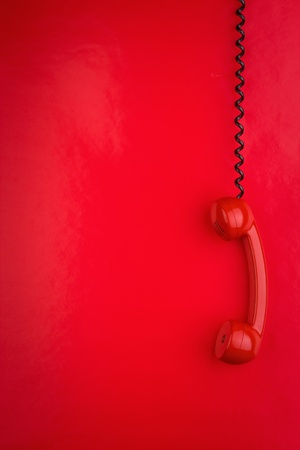 A red telephone hanging by the cord.