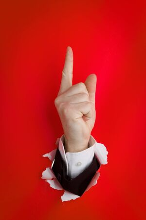 Close of hand with upward pointing finger protruding through hole in red background. Stock Photo - 9711825