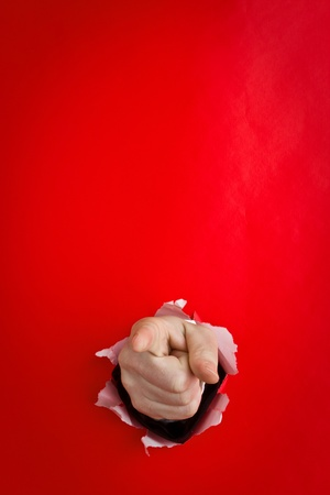 Close up of pointing finger on human hand protruding through torn red background.