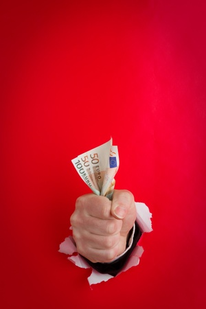 Human fist gripping handful of Euros, against red background Stock Photo