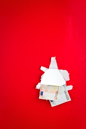 One hundred and fifty Euros in a hole on a red background. photo