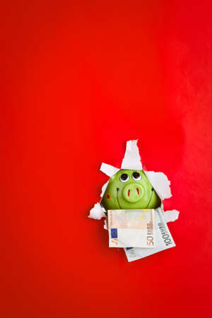 A green piggy bank and money with a red background.  photo
