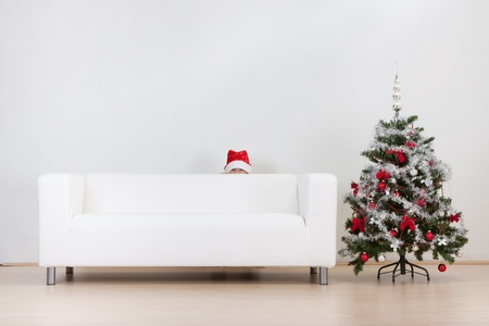 A little boy hiding behind the white couch and a Christmas tree.  photo