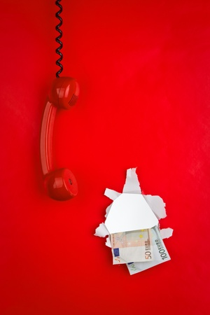 A red phone handing and money through the wall.  photo