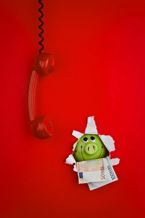 poking: Red phone against red background, with piggy bank and money poking through hole in background Stock Photo