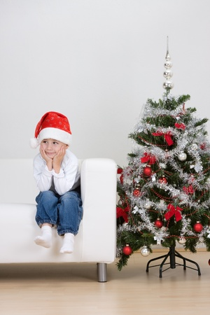 A young toddler boy wearing a Santa hat sitting on a white couch or sofa beside a decorated Christmas tree. photo