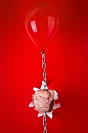 Close up of human hand protruding through hole in red background, holding red balloon on chain. Stock Photo - 9712113