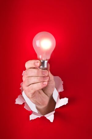 Hand reaching through hole in wall, holding light bulb Stock Photo - 9712128