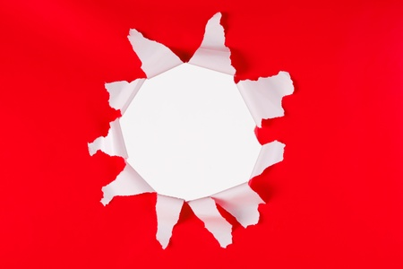 white hole: Close up of exposed white hole torn in red background.