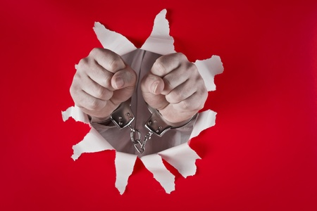 two male fists in shackles on red background Stock Photo - 9712131