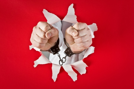 Two fists in shackles on red background Stock Photo - 9712570