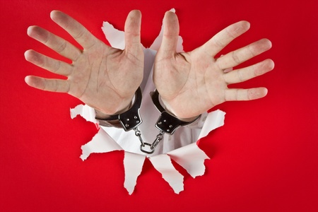symboll: Two male open hands in shackles on red background
