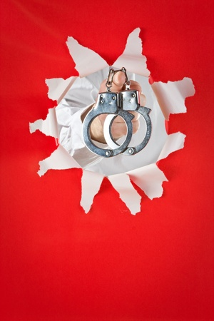 Shackles hang on finger on red background photo