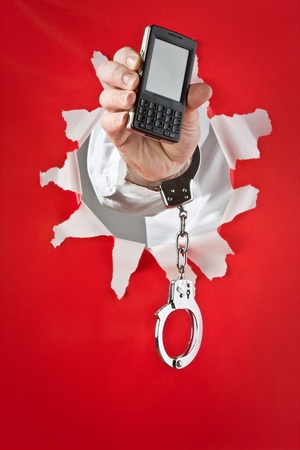 Male hand in shakles hold black mobile telephone on red background Stock Photo - 9712765