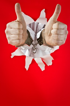 Two male hands in shackles shows ok with thumbs  on red background. Stock Photo - 9712305