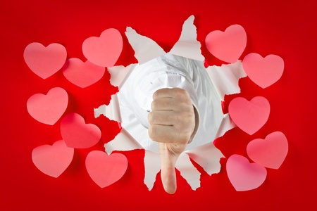disapprove: A view of a fist bursting through a solid red wall with a thumbs down gesture surrounded by Valentines hearts. Stock Photo