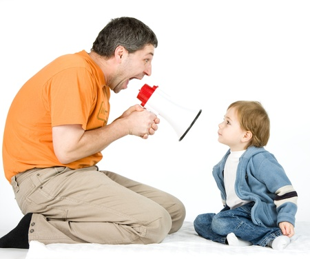 amplified: A studio view of a man with a hand-held, electronic megaphone or bullhorn, yelling at a small boy holding fingers in his ears.