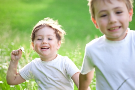 brothers: Two cute young preschool, child running and playing in green field.