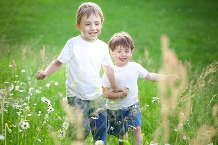 Tow cute preschool siblings holding hands and running through field of long grass.