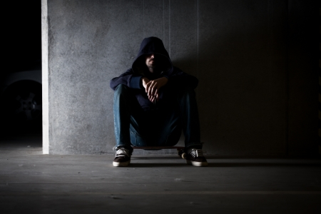 Hooded man sitting against wall. Stock Photo