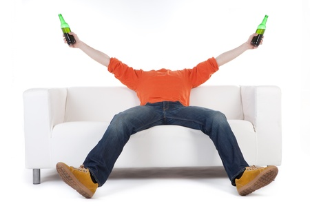 non alcoholic beer: Young man leaning back over a modern white sofa holding two bottles of beer with his arms raised in celebration.