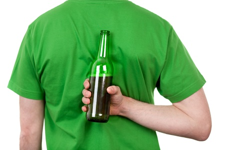Rear view of body of man holding bottle of beer behind back; isolated on white background. photo