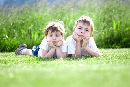 Two cute preschool siblings lying on green grass with field in background.. photo