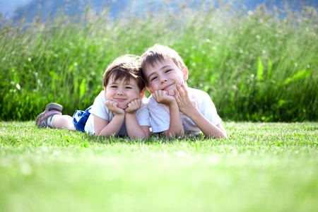 Two cute preschool siblings lying on green grass with field in background.. Stock Photo