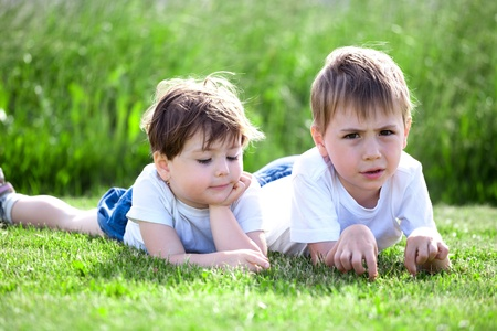 Two cute preschool siblings lying on green grass with field in background.. Stock Photo - 10069879